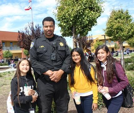 Officer with three students in quad