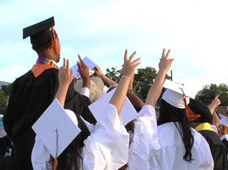 Graduates in cap and gown with arms in the air