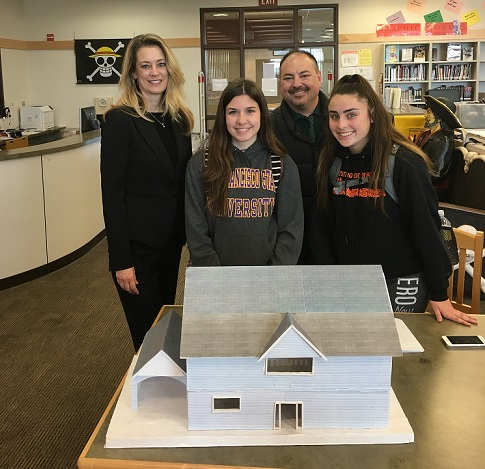 Superintendent Schulze, Anthony Molina, and students pose in front of house model in library