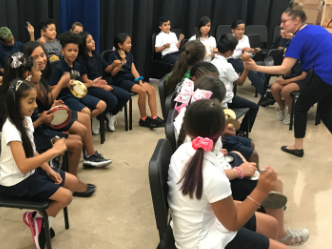 Music teacher interacting with students in chairs